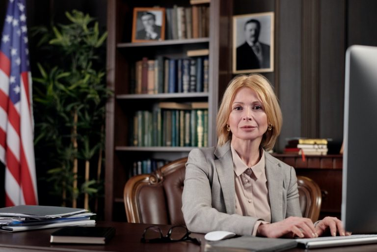 A lawyer sitting in her office with books, plants and a photo frame in the background